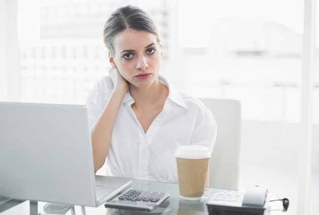 Calm serious businesswoman sitting at her desk