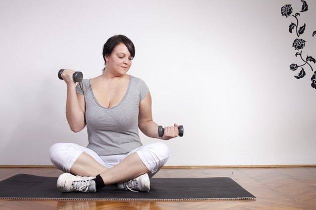 Plus sized woman exercising, lifting weights at home