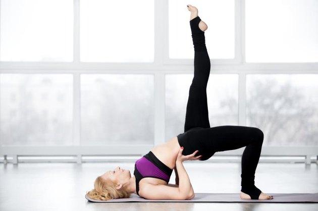 Woman performing a one-legged pelvic tilt Pilates butt exercise