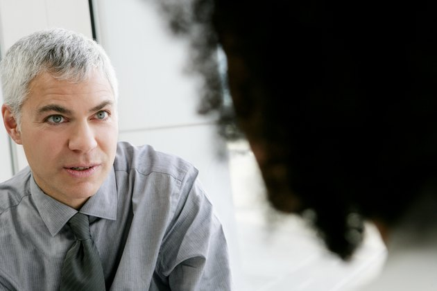 Mature businessman talking with colleage in airport.
