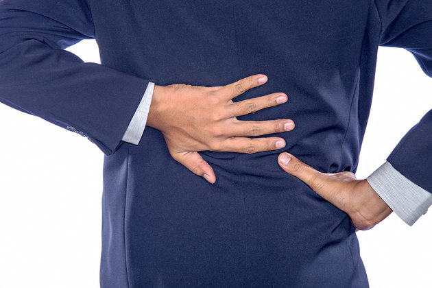 Backache concept bending over in pain with hands holding