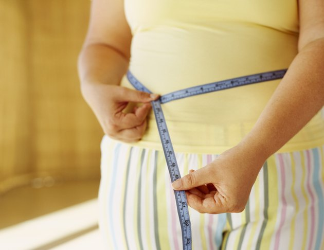 mid section view of a woman measuring her waist