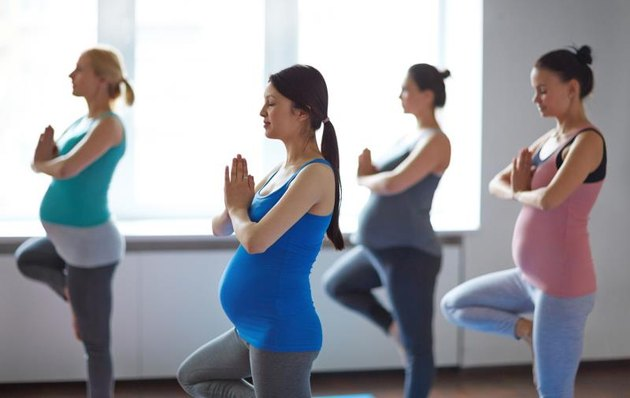 Young pregnant women doing yoga exercise in gym