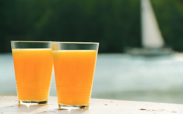 two glasses of orange juice against sea