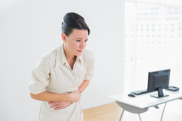 Businesswoman with stomach pain in office