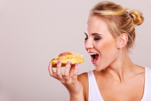 Diet dilemma, grow fat from eating sweets concept. woman holds cake sweet bun in hand, trying to resist temptation, taking a huge bite out of dessert