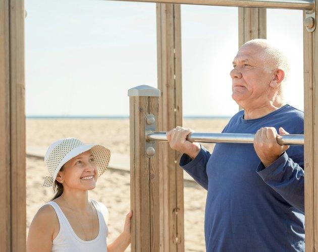 Happy senior couple training on pull-up bar