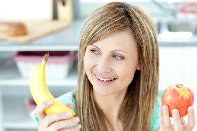 Positive caucasian woman holing a bananan and an apple