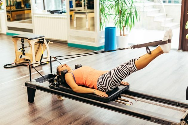 Young woman stretching on a pilates reformer