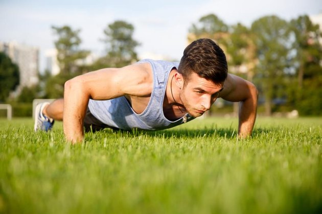 Handsome young man training in park and doing push-ups on green grass
