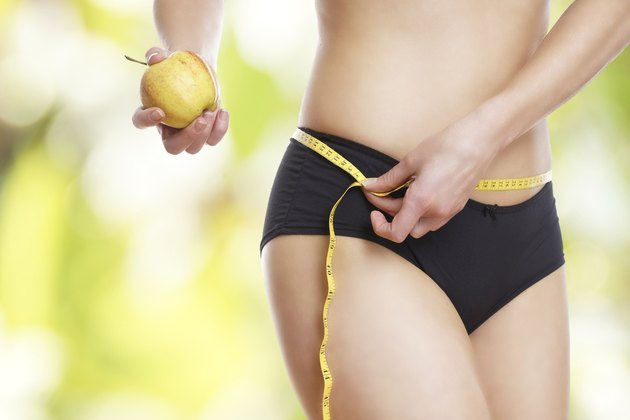 Frau mit Maßband und Apfel