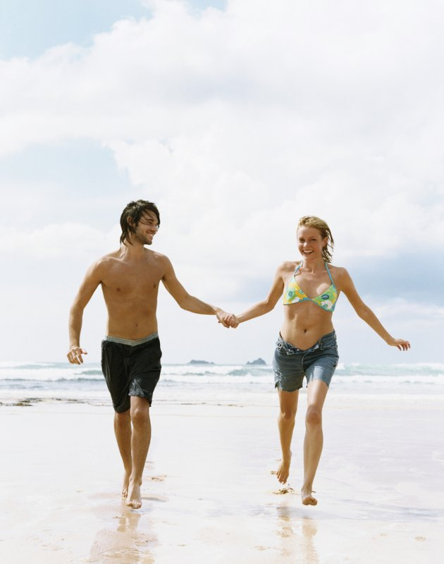 Young Couple in Swimwear Run on the Beach Holding Hands