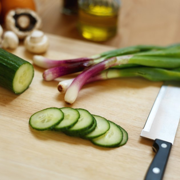 Close up of cucumber slices and onions and mushrooms and a knife lying on a chopping board