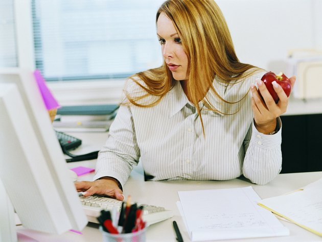 Businesswoman at a Desk Looking at a PC and Eating an Apple