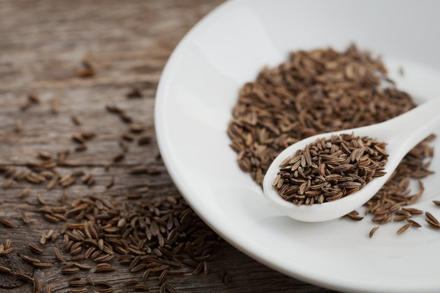 Cumin or caraway seeds on wooden board