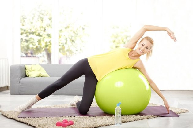 Portrait of beautiful woman doing pilates with exercise ball at home.