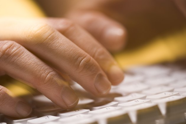 Close-up of person typing on a computer keyboard