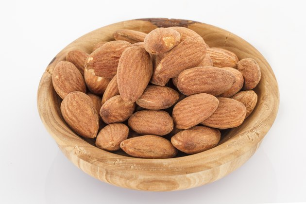 almonds in a wooden bowl isolated on white