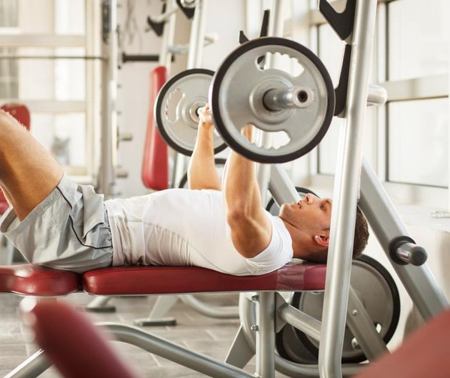 Muscular man lies on a bench and performs heavy weights presses at the fitness center.