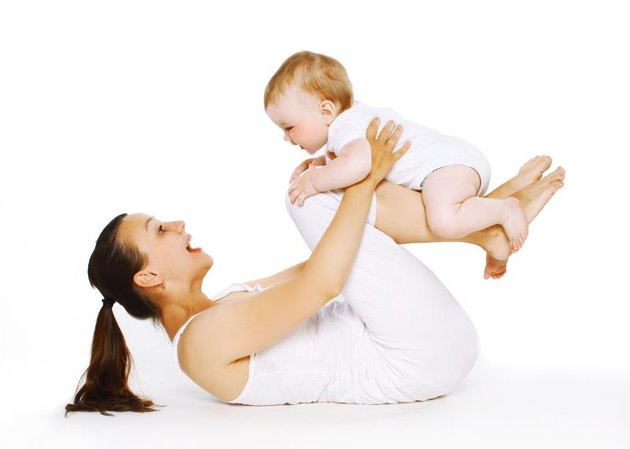 Mother and baby are doing exercise, gymnastics, fitness, play - concept