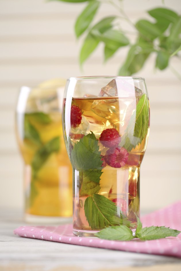 Iced tea with raspberries, lemon and mint on wooden table
