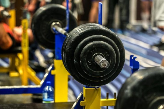 Barbells set up for a bench press in a gym.
