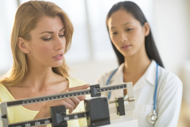 Woman Adjusting Weight Scale While Standing By Female Doctor