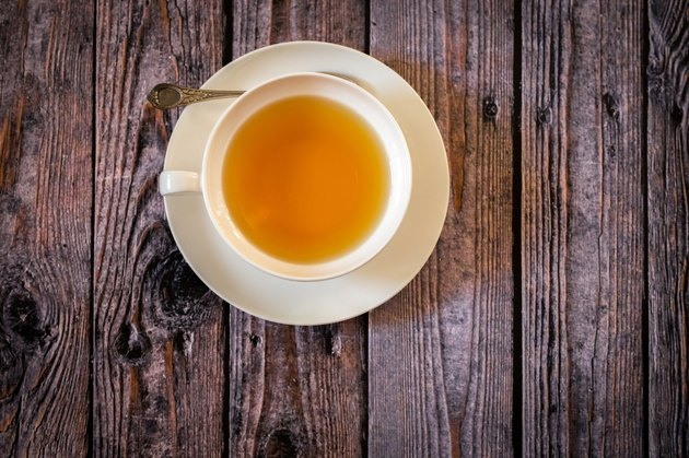 Cup of tea on wooden background, top view