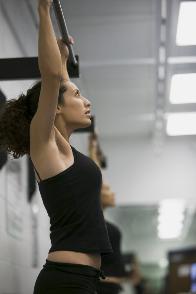 fitness lifestyle shot of a young adult woman in a workout outfit as she does pull ups