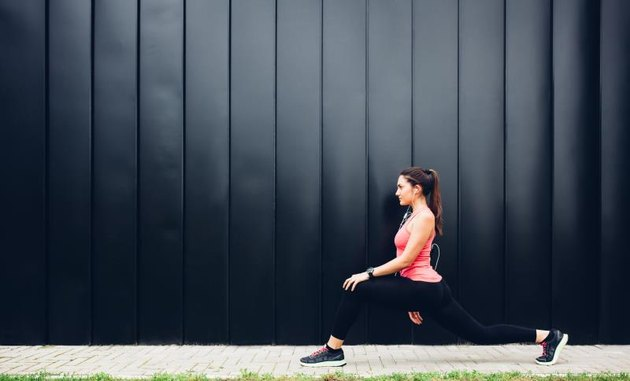 Beautiful young woman doing exercises in front of a black wall