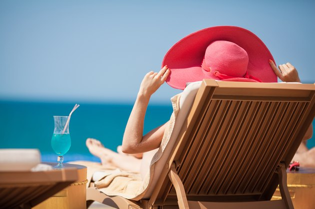 Woman in hat on a sun lounger near the sea