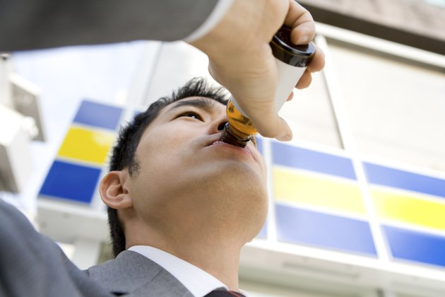 Man drinking energy drink in front of convenience store