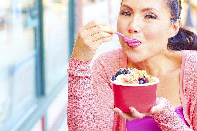 Happy Young Pretty Mixed Race Female Eating Frozen Yogurt