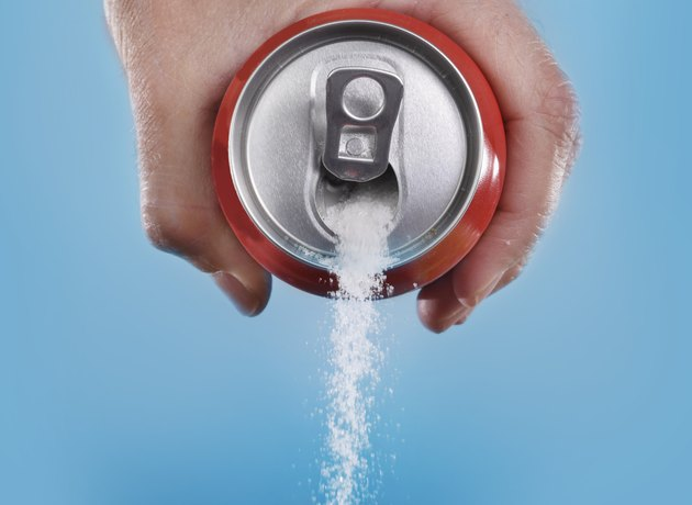 hand holding soda can pouring in metaphor of sugar content
