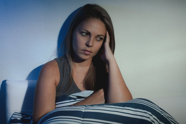 Insomnia. woman sitting on the bed awake with hands on head