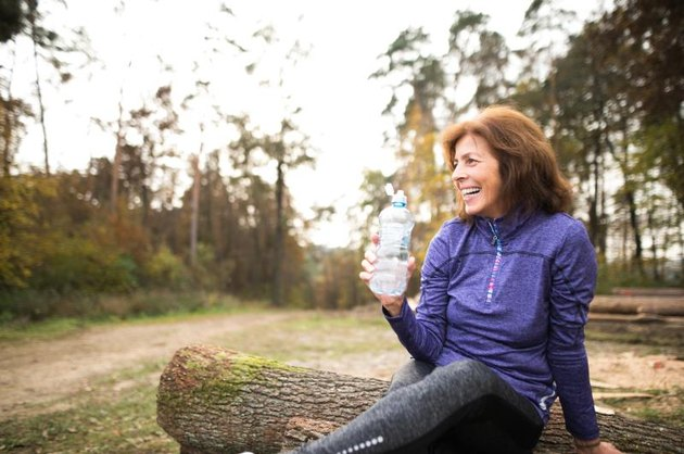 Senior runner in nature. Woman sitting on wooden logs, resting, holding water bottle.