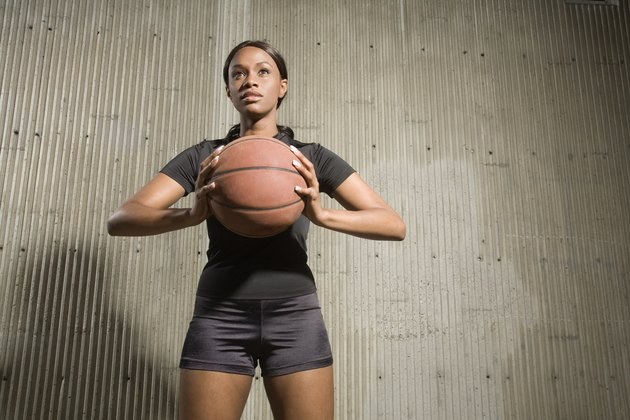 Portrait of young woman holding a basketball, photographed from a low perspective