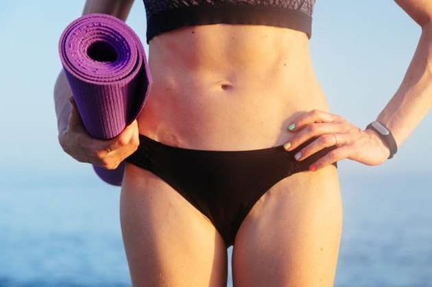 Sportive leisure woman with perfect body holding yoga mat. Health life concept. Toned image.