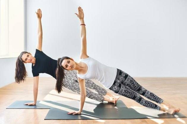 Two young women doing yoga asana side plank. Vasisthasana