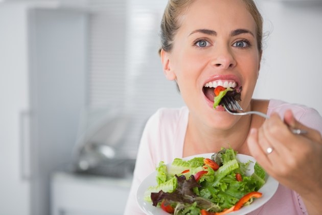 Casual blonde posing while eating salad