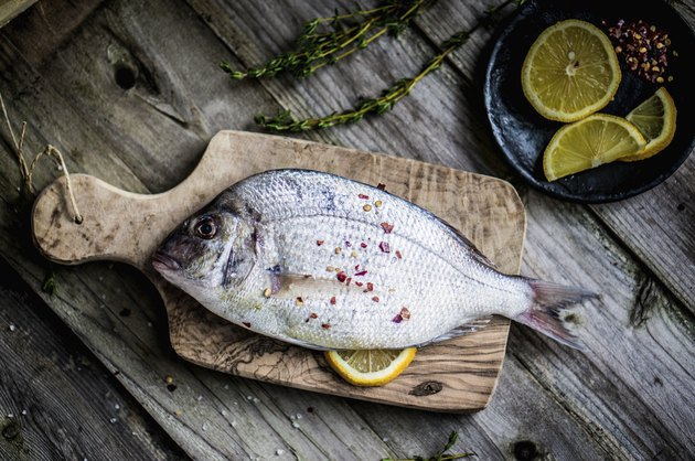 Fresh sea bream on wooden board