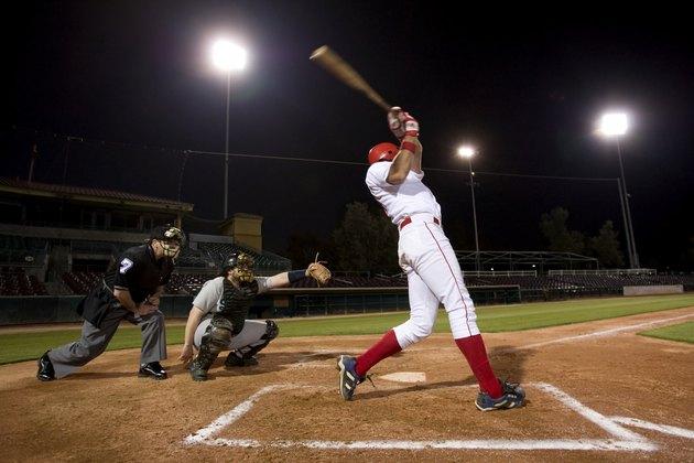 USA, California, San Bernardino, baseball players with batter swinging