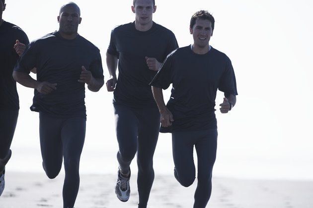 Four men jogging on beach