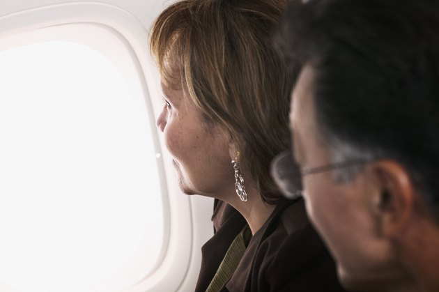 Mid adult couple looking out of a window in an airplane