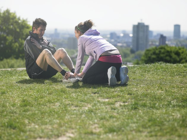 Woman helping man doing sit-ups on grass, city in background