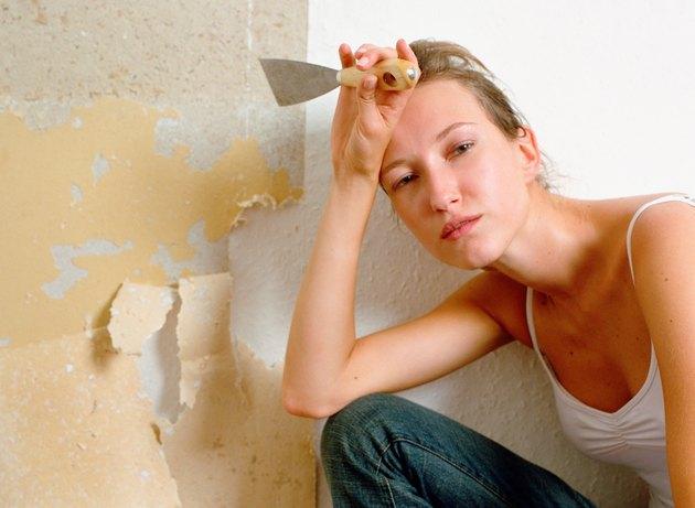 Tired woman holding scraper