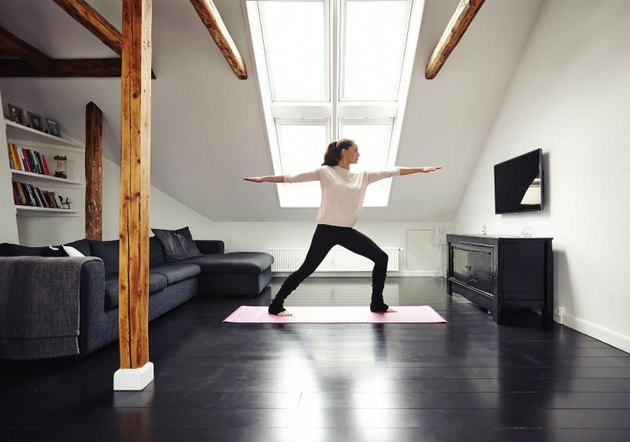 Full length image of fit woman standing on exercise mat with arms outstretched doing yoga in loving room. Caucasian female model exercising at home.