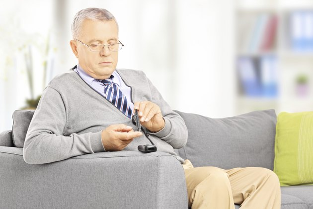 Mature on sofa measuring sugar level at home