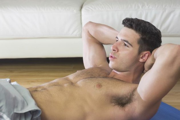Determined handsome man doing sit ups in bright living room