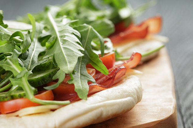 rustic sandwiches with ham arugula and tomatoes in pita bread